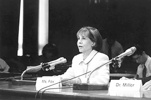Ms. Fox sits, speaking into the microphone in front of her, at a conference table in a Congressional hearing room.