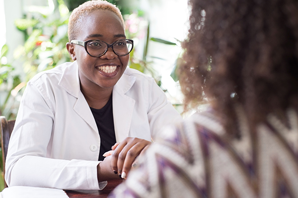 Young female doctor smiling at female patient in doctor's office.