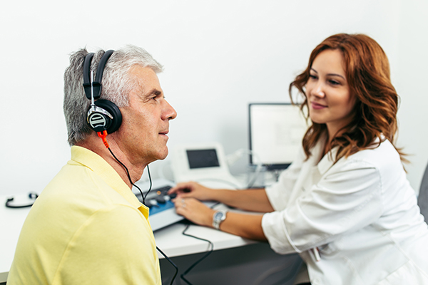 Young female audiologist giving hearing test to senior male in doctor's office.