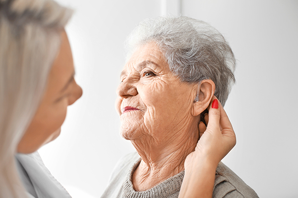 Young female doctor fitting hearing aid on older female's ear.